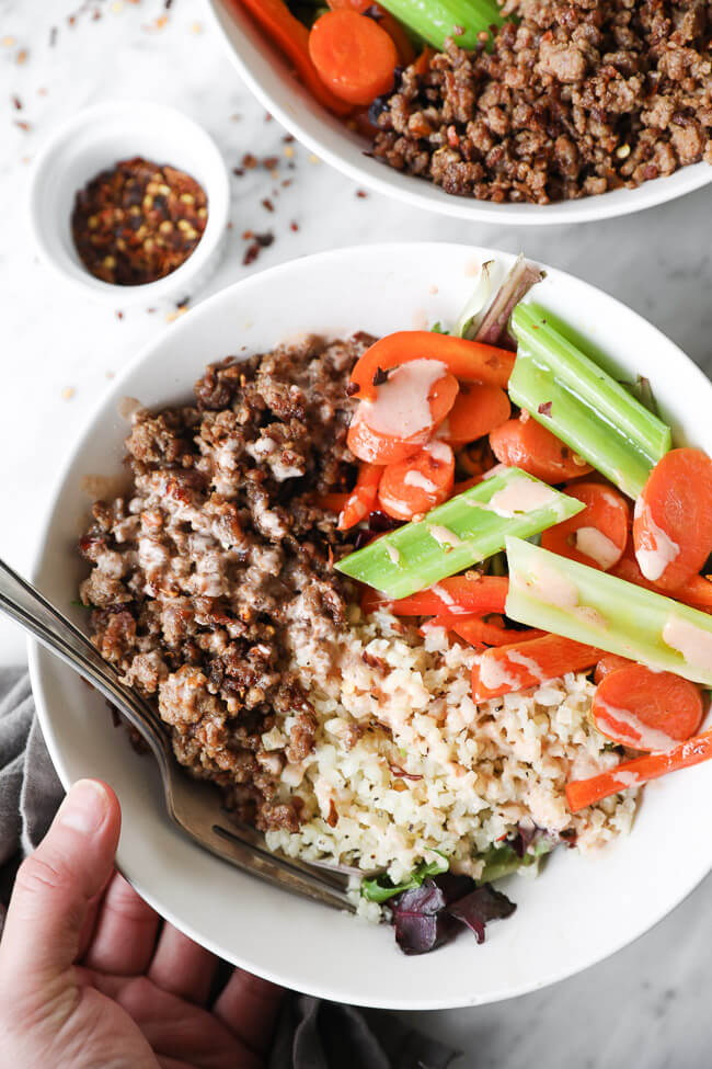 Overhead close up image of holding a bowl of spicy pork, cauliflower rice and veggies.