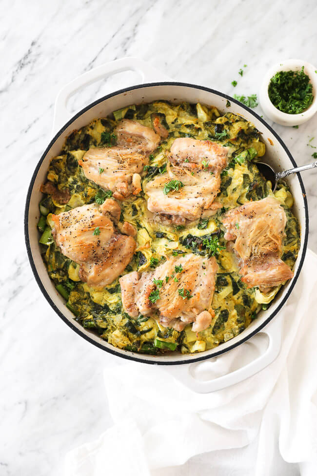 Vertical overhead image of spinach artichoke chicken in a skillet with a serving spoon dug in. Chopped parsley in a small bowl on the side.