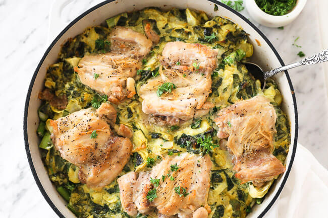 Horizontal image of spinach artichoke chicken in skillet with serving spoon dug in. Topped with chopped parsley.