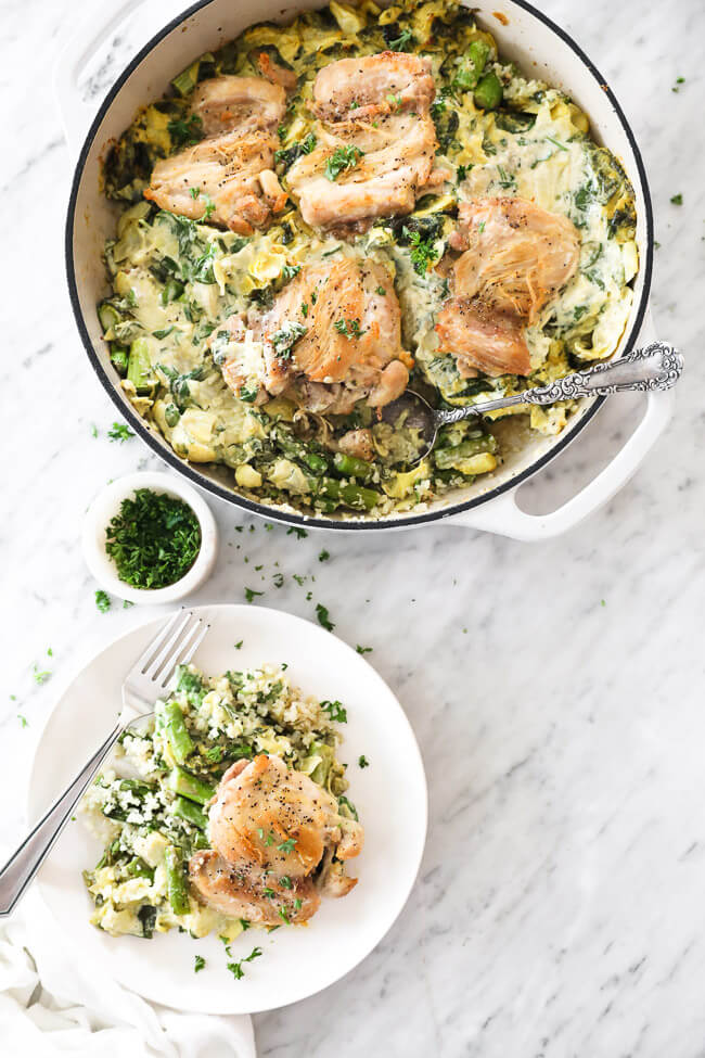 Vertical overhead image of spinach artichoke chicken in a skillet with serving spoon and some served up on a plate with a fork. Chopped parsley to garnish on the side.