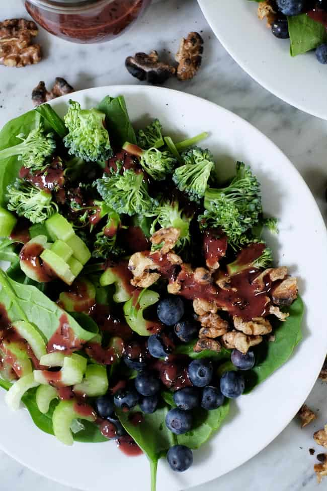 Spinach blueberry salad on plates with extra walnuts and blueberries spread around and blueberry dressing on the side.