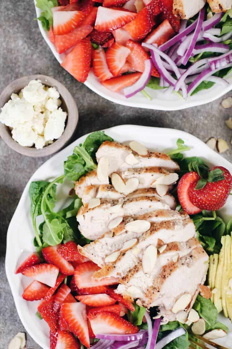 In just 30 minutes this Paleo + Whole30 savory and sweet strawberry chicken salad will be on the table! It's full of flavor and super easy to make! Simple chicken pairs perfectly with arugula, spinach, strawberries, avocado, red onion, sliced almonds and an easy balsamic dressing. Paleo + Whole30 | realsimplegood.com