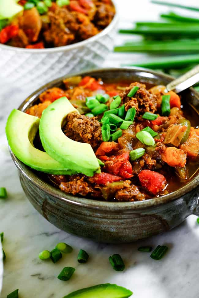 Angled shot of Paleo + Whole30 sweet potato chili in a bowl with chopped green onion and avocado slices.