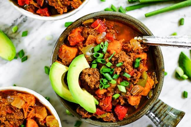 Paleo + Whole30 sweet potato chili served up in bowls with chopped green onion and avocado slices.