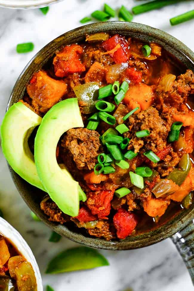 Close up shot of Paleo + Whole30 sweet potato chili with chopped green onion and avocado slices on top.