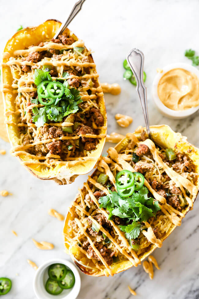 Two taco stuffed spaghetti squash with sauce drizzled on top and spoons coming out of the squash