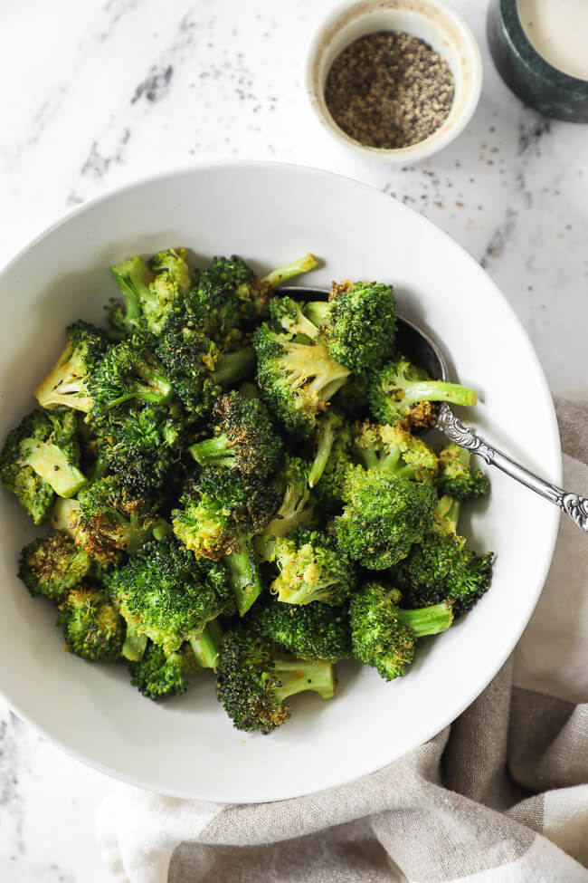 Bowl full of air fried broccoli with a serving spoon.