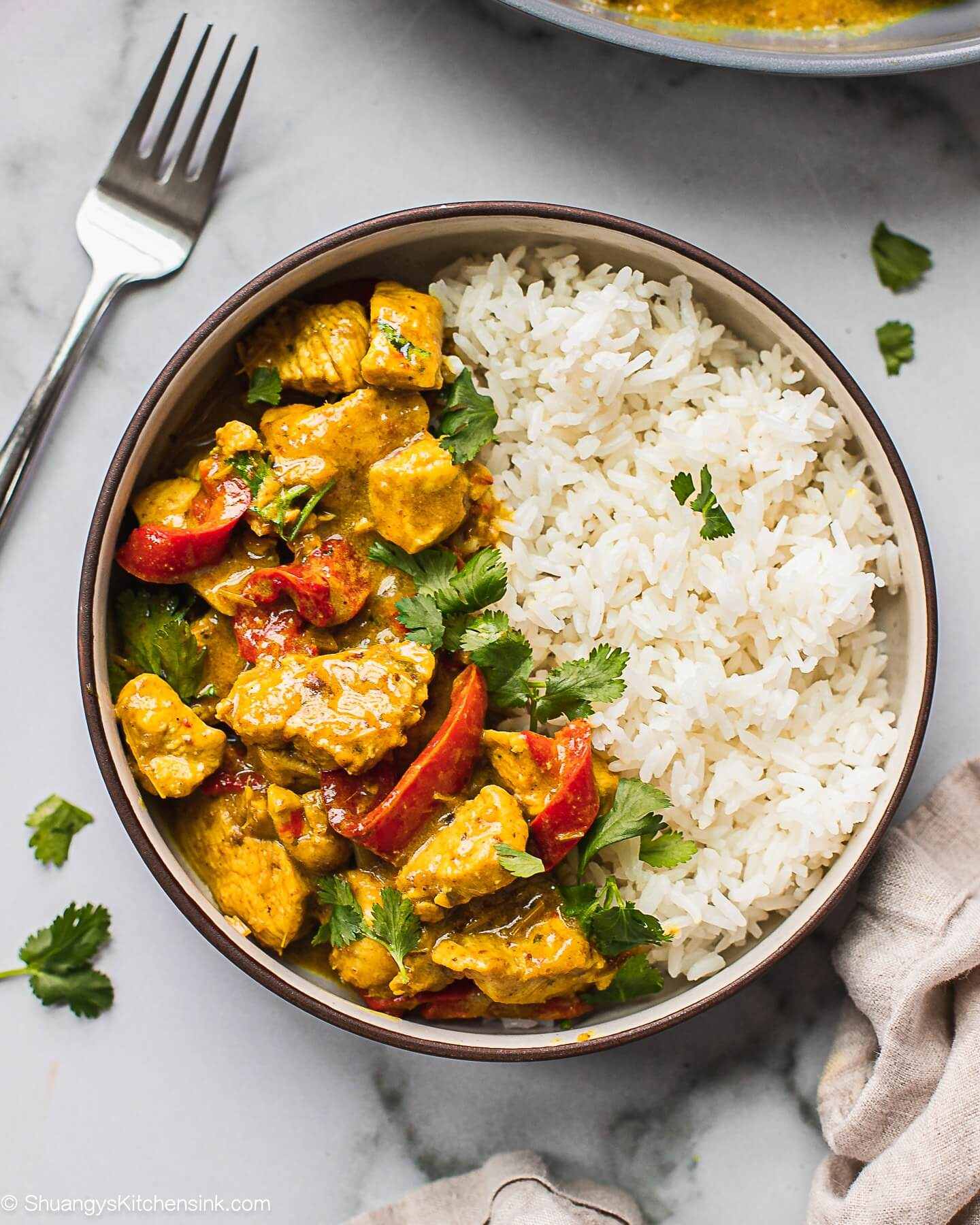 Thai coconut curry in a bowl with red peppers and rice