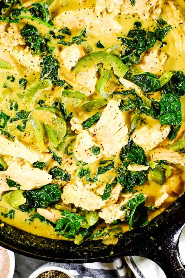 Close up shot of Thai coconut curry in cast iron skillet. Chicken, onion, bell pepper and kale in a creamy curry sauce.