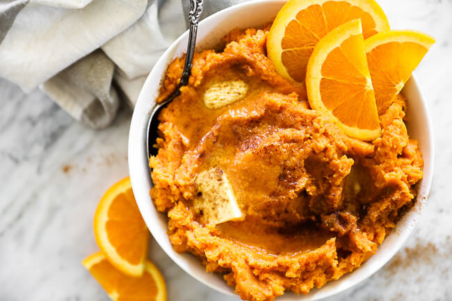 Horizontal overhead image of Thanksgiving yams in a bowl with a serving spoon. Melted butter and cinnamon on top with orange slices as a garnish.