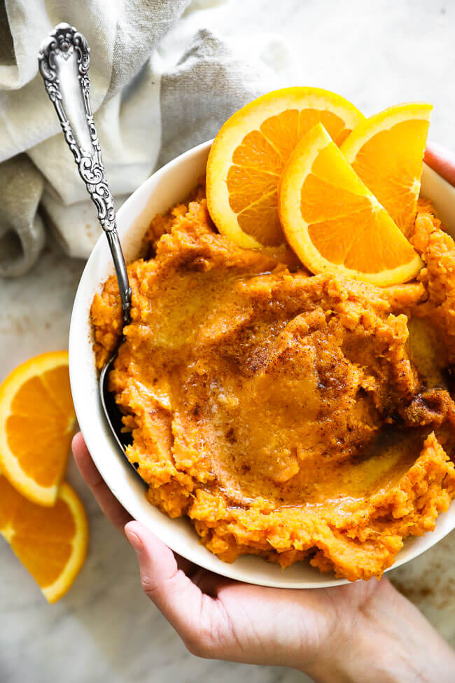 Vertical overhead image of holding a bowl full of Thanksgiving yams with a serving spoon dipped in. Melted butter and cinnamon on top. Orange slices as a garnish.