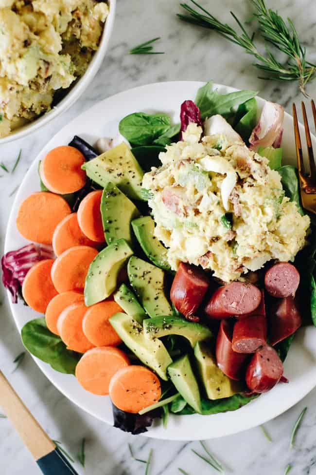 The best potato salad with bacon on a plate with greens, carrots, avocado and sausage.