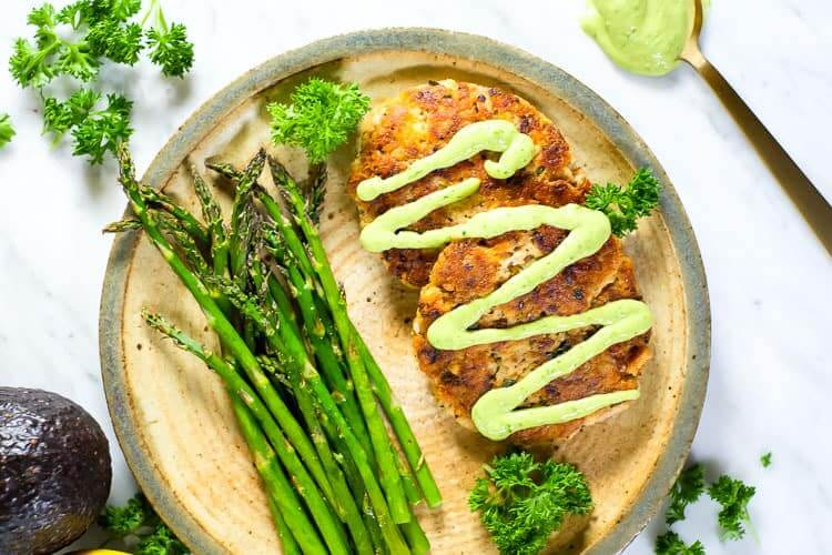 Horizontal best salmon patties with magic green sauce, asparagus and parsley garnish.