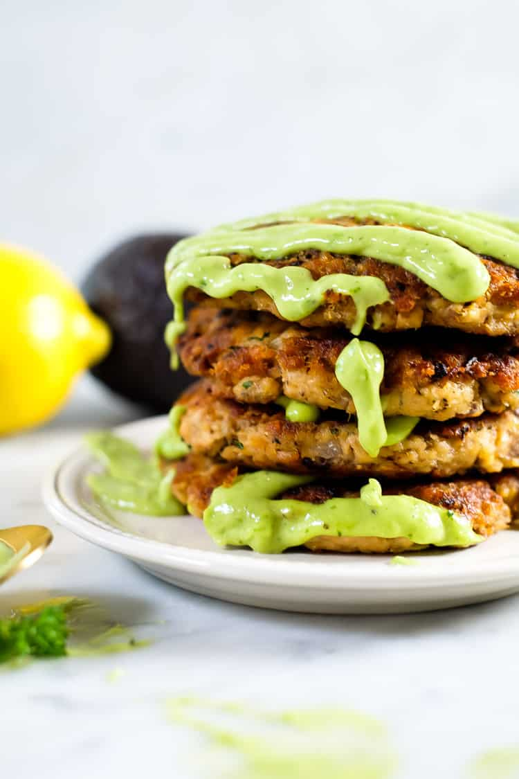 The best salmon patties stack with green sauce drizzle cascading down.