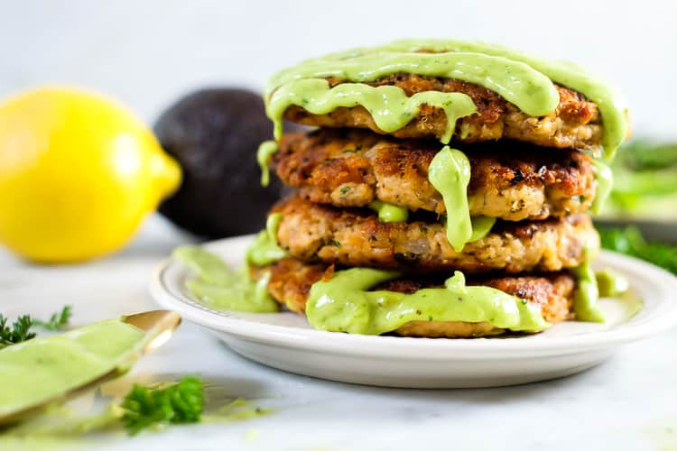 the best salmon patties stacked with green sauce. Avocado and lemon.