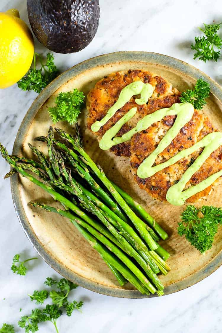 the best salmon patties, green sauce and asparagus. lemon, asparagus and parsley.