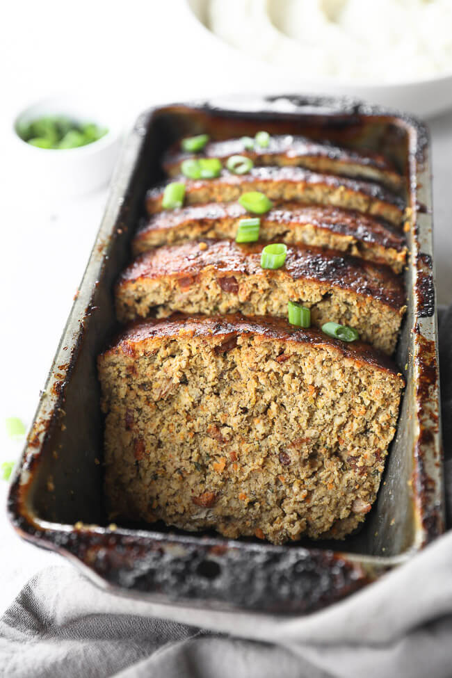 Close up angle image of chicken meatloaf slices in a loaf pan with green onion on top