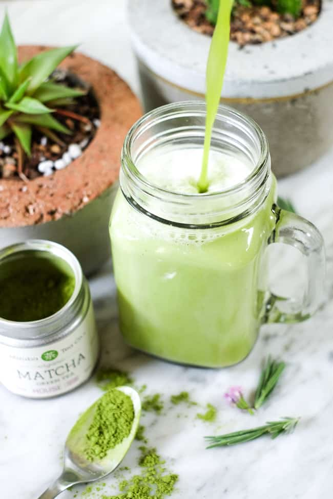 Pouring iced matcha latte into mason jar mug with succulents in the background.