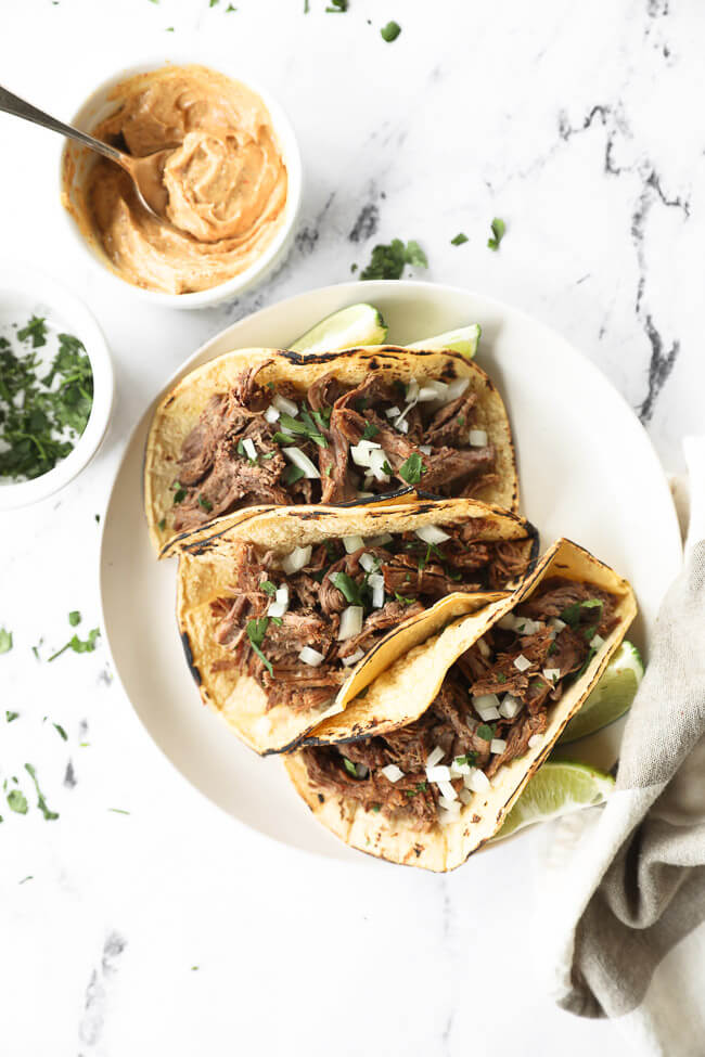 Shredded beef tacos on a plate with chopped onion and cilantro topping and sauce on the side