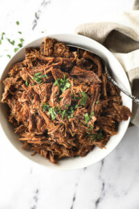 Instant pot shredded beef in a white bowl with chopped parsley topping