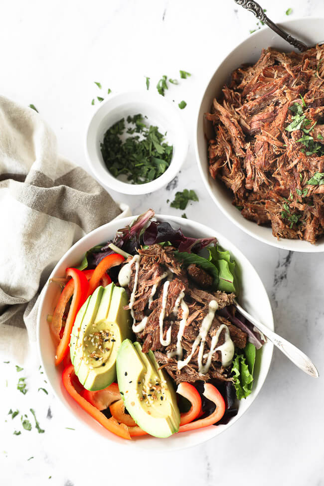 Shredded beef in a bowl over greens with red bell pepper, avocado and sauce drizzled on top