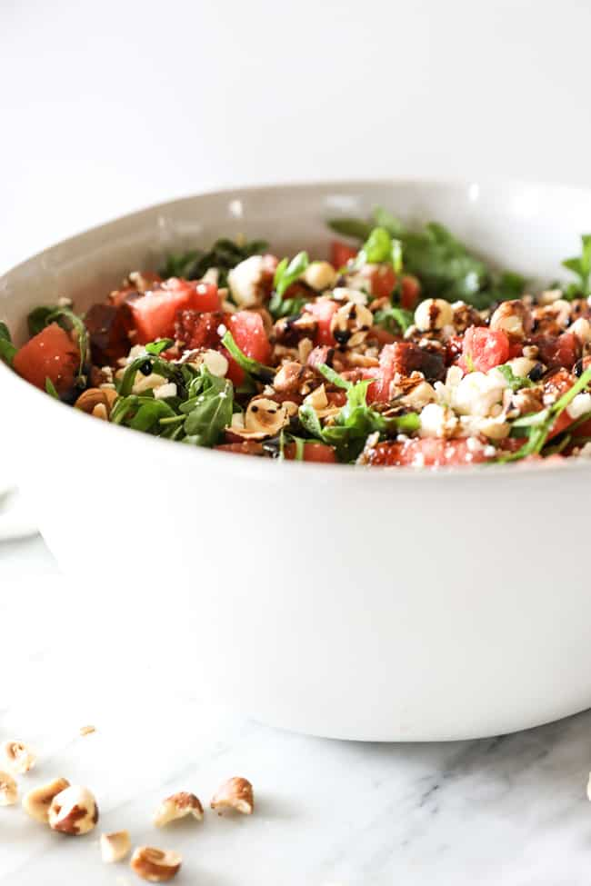 Angled vertical image of watermelon salad in a large serving bowl. Watermelon, arugula, hazelnuts, balsamic vinegar and optional feta cheese.