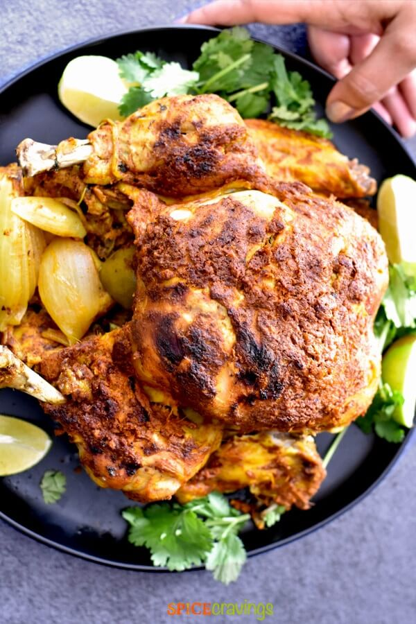 Whole browned cooked chicken on a black palate with parsley and lemon