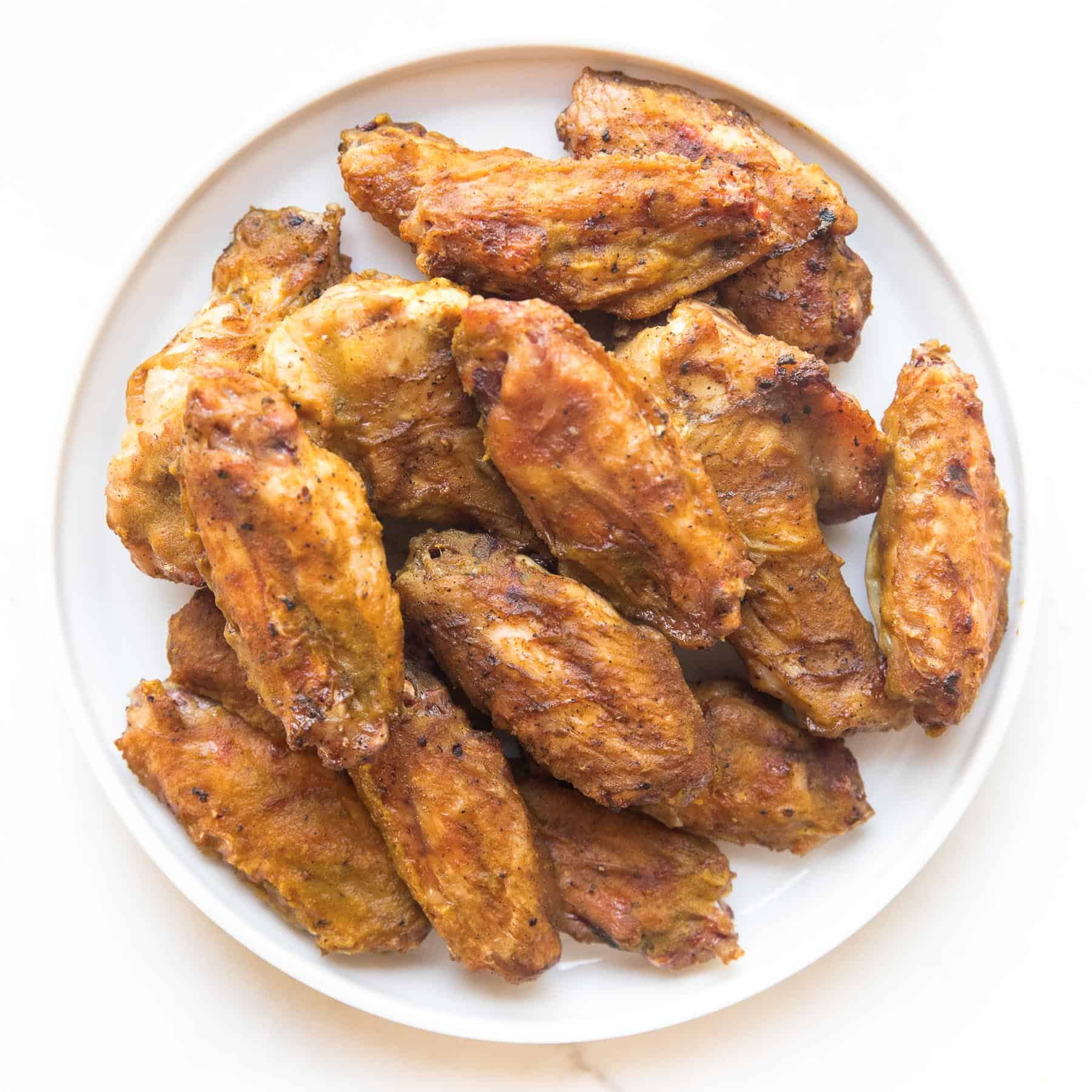 Overhead shot of a pile of grilled chicken wings on a white plate