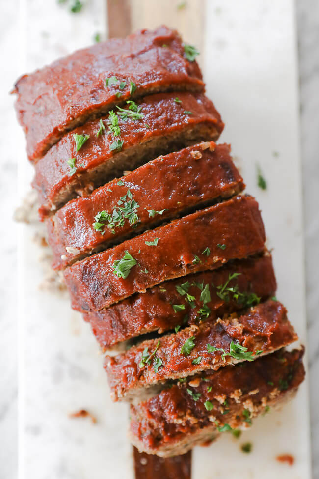 Slices of Whole30 Paleo Meatloaf with ketchup on top on a board overhead image