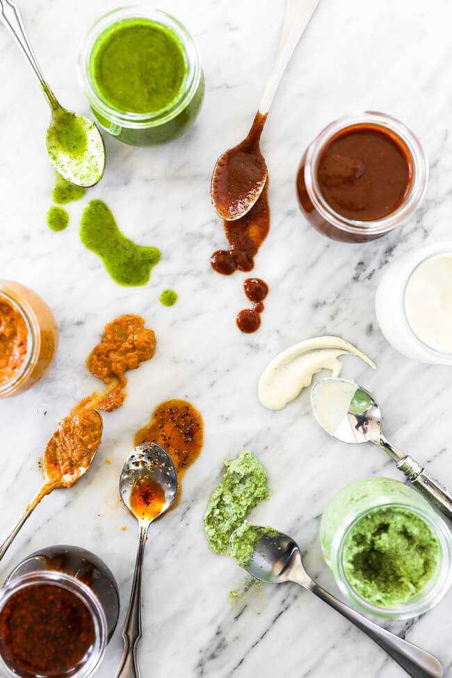6 easy whole30 sauces in jars overhead shot. Spoons on marble with sauces on them