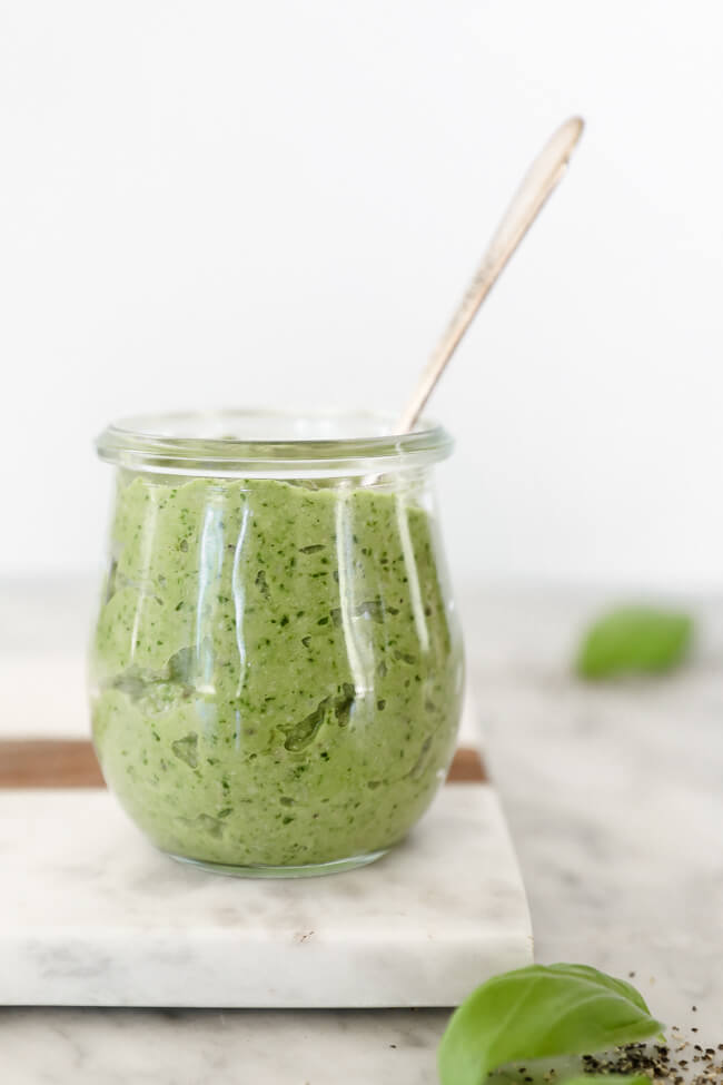 Whole30 cheesy pesto sauce in jar with spoon coming out straight on shot