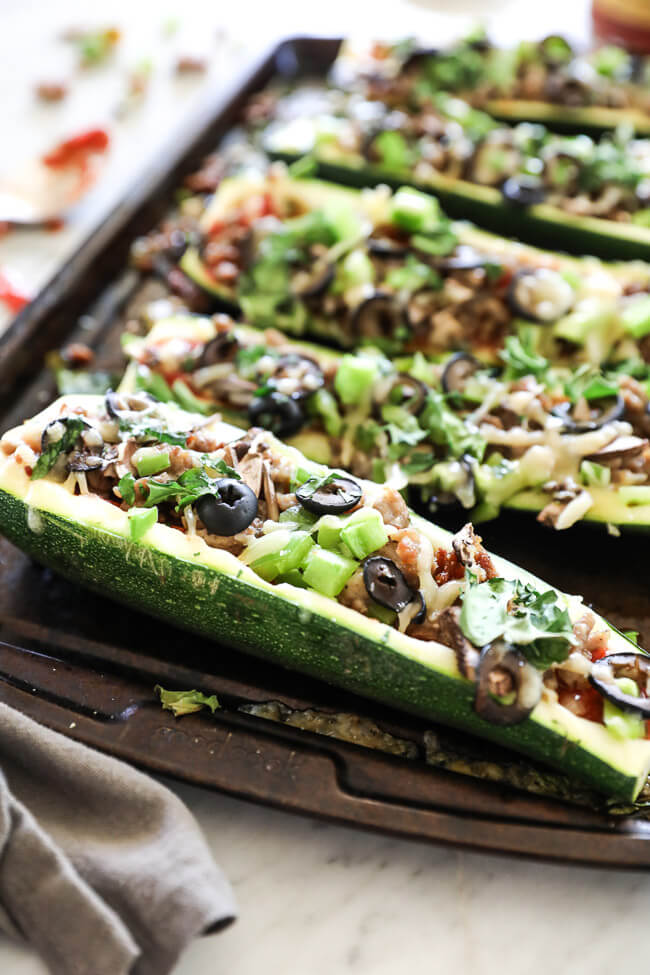 Angled vertical image of zucchini pizza boats on sheet pan. Loaded with marinara sauce, italian sausage, bell pepper, mushrooms, olives and cheese. Fresh basil sprinkled on top.
