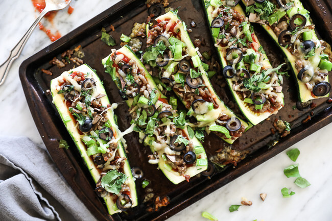 Overhead horizontal image of zucchini pizza boats on sheet pan. Loaded with marinara sauce, italian sausage, bell pepper, mushrooms, olives and cheese. Fresh basil sprinkled on top.