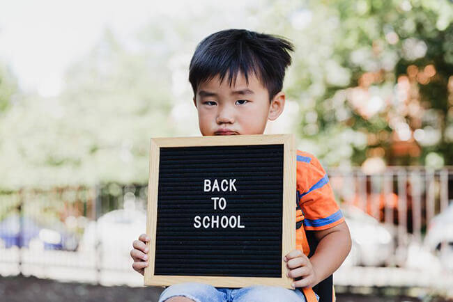 Grumpy child holding sign saying back to school