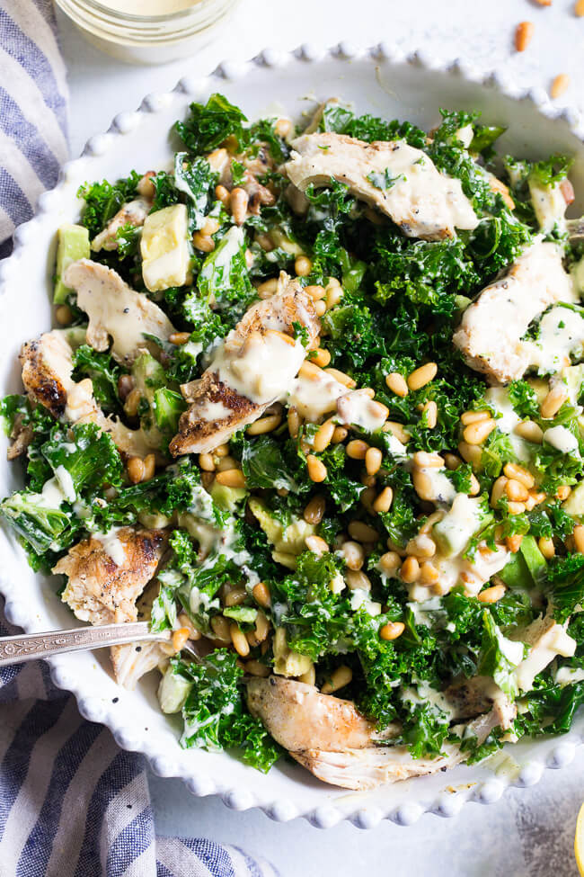 Kale chicken caesar salad in white bowl with pine nuts on top