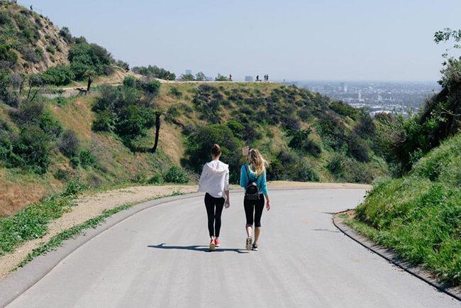 Two women walking down a road outside