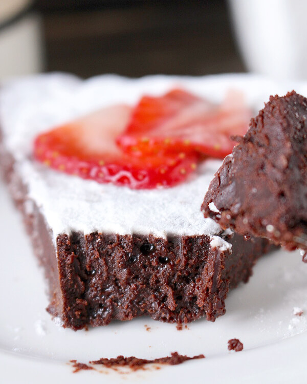 Close up of flourless chocolate cake with sliced strawberry on top