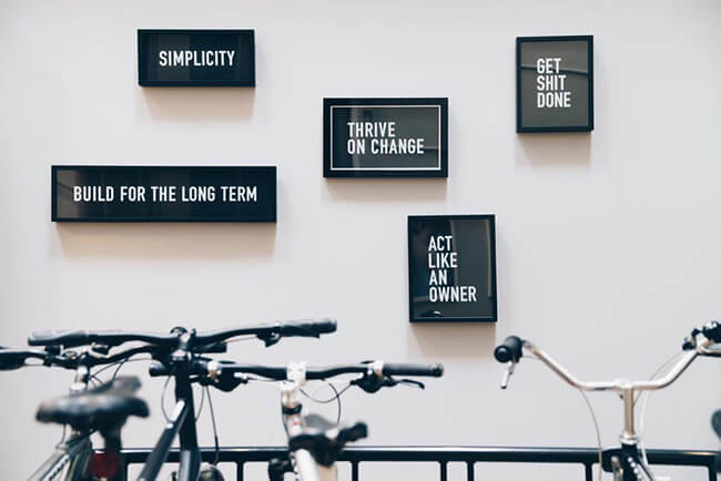 Framed quotes on white wall above bikes