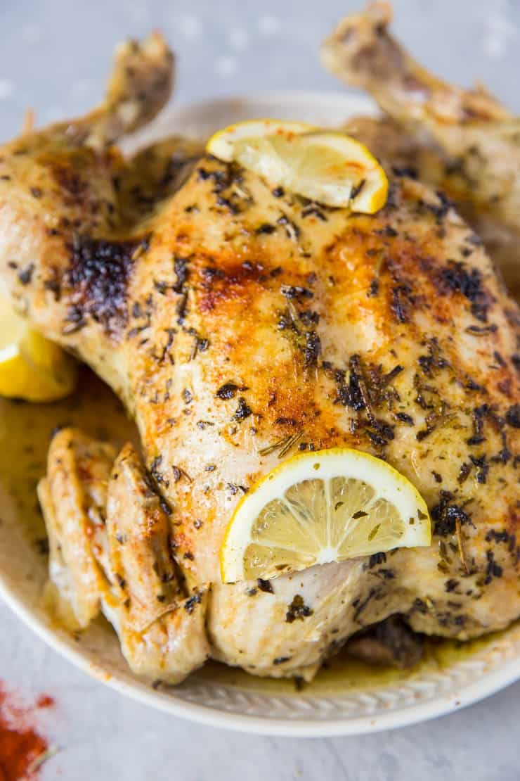 Whole lemon herb cooked chicken on a white plate