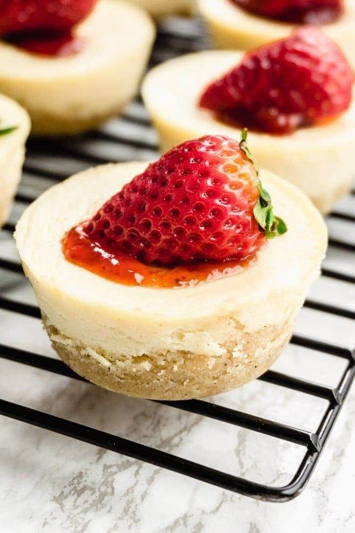 Mini cheesecake on a cooling try with strawberry on top