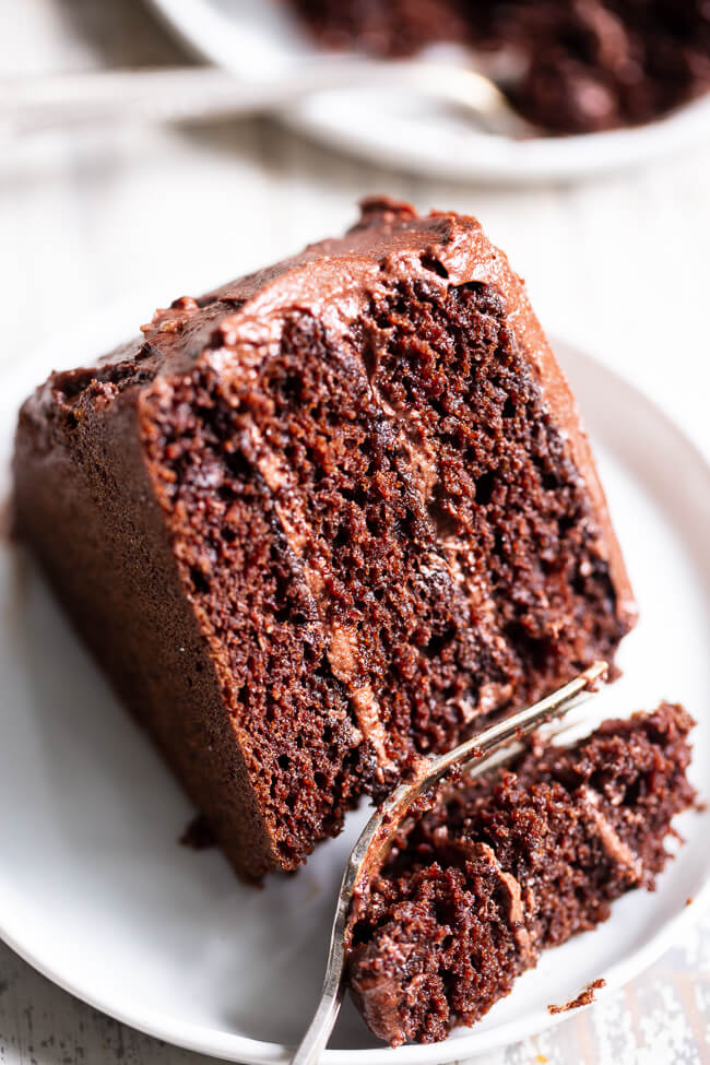 Slice of chocolate cake with frosting and a fork taking a bite out