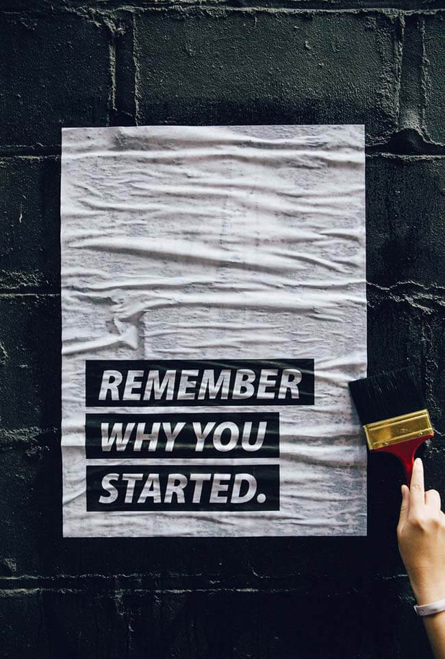 Poster on brick wall saying remember why you started