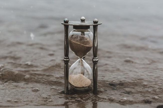 Hourglass on sand with water