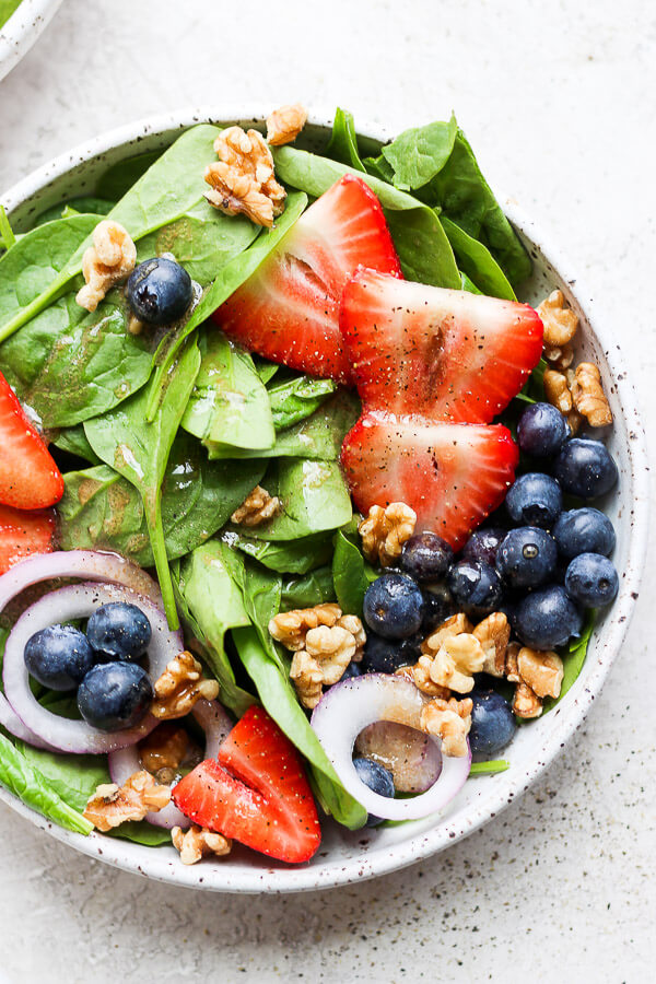 spinach salad with sliced strawberries, blueberries, walnuts and onion on top