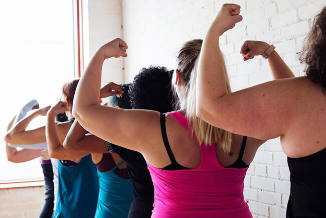 Women in a line flexing their arms