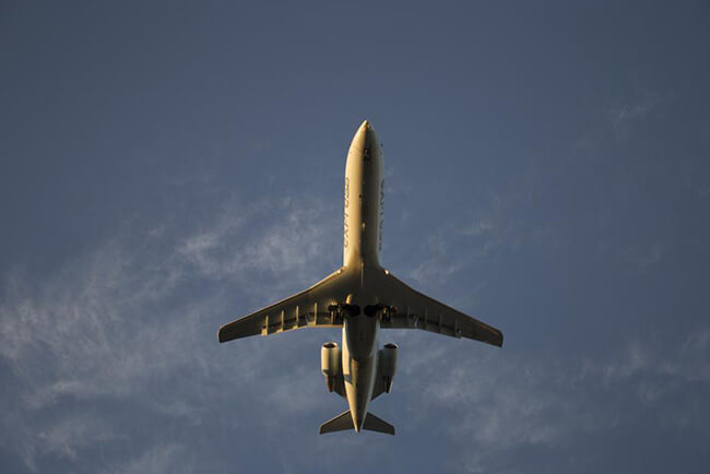 Image of plane flying with blue sky