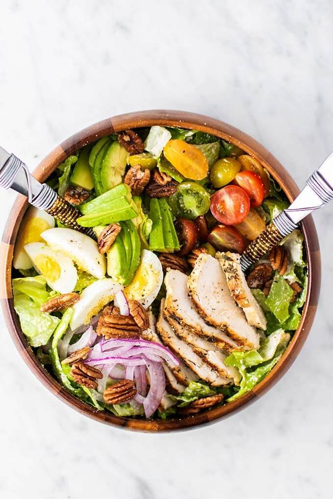 Chopped chicken caesar salad in bowl with tomato, egg, tomato, purple onion and avocado